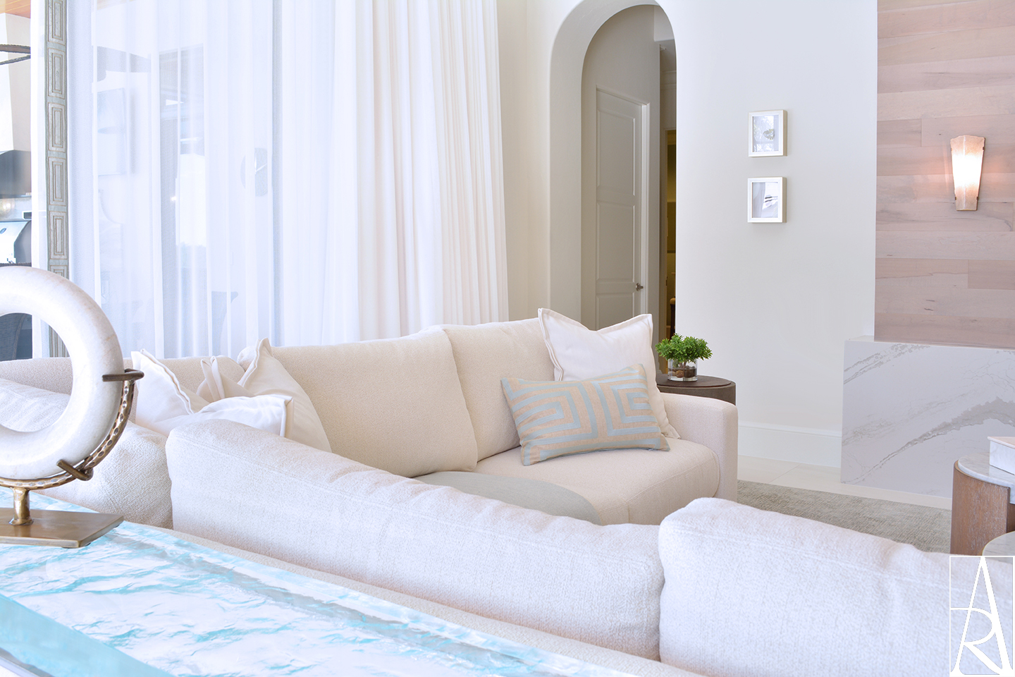 A contemporary living room interior design with linen sofa and a textured glass table