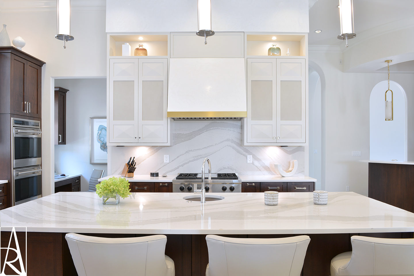 A transitional kitchen design with two tone cabinets and quartz waterfall island countertop