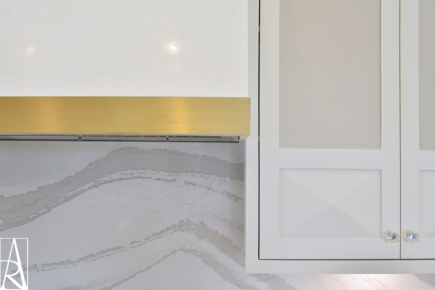 Closeup detail of leather insert cabinets, X cabinet detail, white plaster hood with brass hood trim